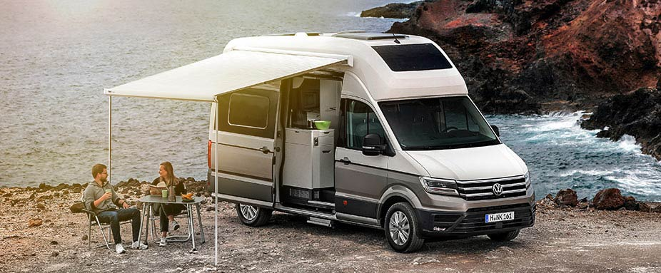 VW Grand California stehend am Meer